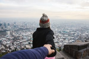 A man holds a woman's hand as she peers over the roof of a skyscraper.