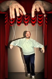 A puppeteer's stage showing the puppeteer's finders attached to strings that are connected to a living man the puppeteer can move.