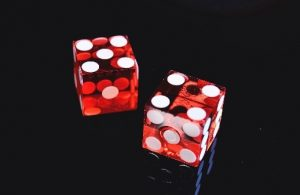 Clear red dice showing four and five on black surface