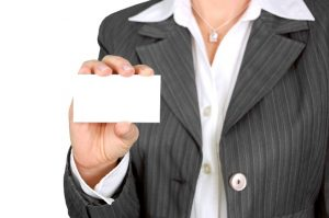 Torso of a woman in a suite with a business card, facing outward,  in her right hand